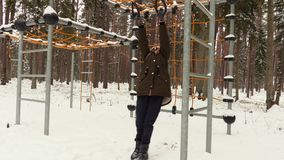 Girl try to hanging on monkey bars. In winter day stock footage