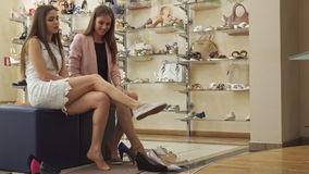 Girl tryes on slippers at the shop. Attractive brown haired girl trying on slippers at the shop. Pretty female buyer showing her friend shoes which she choosing stock video