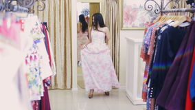 Girl trying on a dress in front of a mirror in a store. Girl in front of a mirror in a dress store stock footage