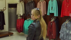 Girl trying on a leather jacket in the store. Girl trying on a leather jacket in the store in front of the mirror. Shopping stock video footage