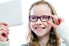 Girl trying new glasses. Royalty Free Stock Photography