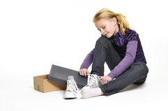 Girl trying on new shoes. Girl sat next to open shoebox trying on new shoes, isolated on white background Stock Photos