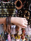 Girl trying out bangles bracelets at bazaar Royalty Free Stock Photos