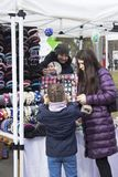 Girl trying on the rim, a woman with dark hair and an eggplant jacket looking at the child, the seller holds a mirror royalty free stock photography