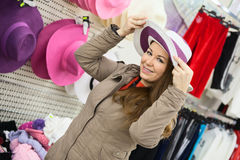 Girl trying on summer hat in shop Royalty Free Stock Images