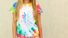 Girl trying on a t-shirt painted in the style of tie dye. Stock Photography
