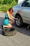 Girl is trying to change a tire Royalty Free Stock Photography