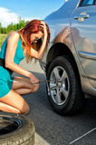 Girl is trying to change a tire Stock Images