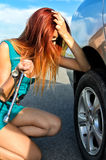 Girl is trying to change a tire Royalty Free Stock Images