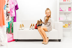 Girl trying to choose shoes among many Royalty Free Stock Photos