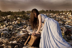 The girl is trying to close the old suitcase in the garbage dump Royalty Free Stock Images