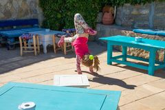 Girl trying to do the somersault in a roof. Four years old blonde girl trying to do the somersault or handstand on floor of a roof with tables royalty free stock photography