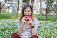 Girl trying to eat her wallet in a park Stock Image