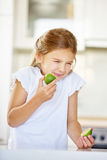 Girl trying to eat lime fruit Royalty Free Stock Photo