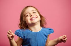 Girl trying to frighten someone with stretched hands. Young cute lady with hazel eyes, dressed in dress, showing teeth and smiling royalty free stock photos