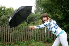 Girl trying to hold an umbrella Royalty Free Stock Image