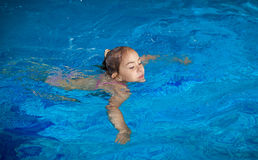 Girl trying to hold on water surface at swimming pool Stock Photos