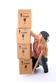Girl trying to lift a stack of cardboard boxes royalty free stock image