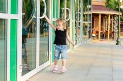 Girl trying to open the doors. Little girl trying to open the doors to the building Royalty Free Stock Photo