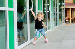 Girl trying to open the doors. Little girl trying to open the doors to the building Stock Photography