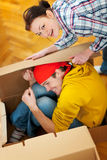 Girl trying to pack boyfriend in cardboard box Royalty Free Stock Images
