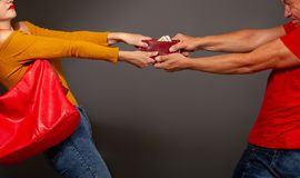 Robber takes wallet. The girl is trying to prevent a robber who wants to pull a purse with money out of her hands stock photo