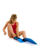 Girl trying to put on flippers Stock Images