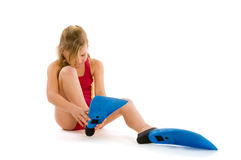 Girl trying to put on flippers Royalty Free Stock Photography