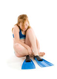 Girl trying to put on flippers Stock Photos