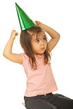 Girl trying to put party hat. Girl looking away and trying to put a green party hat on her head isolated on white background royalty free stock photo