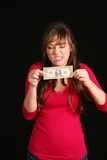 Girl trying to stretch dollar bill Royalty Free Stock Photo