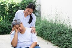 The girl is trying to take care a patient man in a wheelchair, he has a headache. They are a couple royalty free stock image