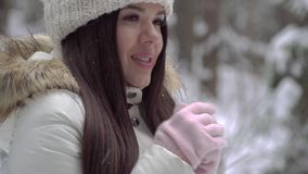 The girl is trying to warm her hands in the winter forest. Beautiful girl with long dark hair in a white jacket walking in a winte stock footage