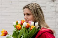 Girl with tulips. On white brick wall Royalty Free Stock Photography