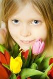 Girl and tulps Stock Photos
