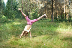 Girl tumbles on the grass. Girl tumbles somersault on the grass Stock Images