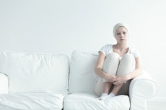 Girl with tumor holding knees Stock Image