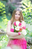 Girl with the tupils. Young girl in the pink dress is holding some tupils in the forest Stock Image