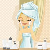 Girl in turban washes facial wash  in the bathroom Royalty Free Stock Photo