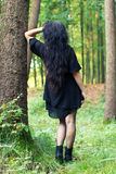 Girl turned around standing and leaning on a tree Royalty Free Stock Photos