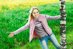 The girl is turned round a birch. The young beautiful woman laughs plays the nature, being turned round a tree Stock Photos