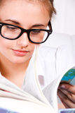 Girl turning book pages. Portrait of a teenage girl in glasses turning book pages royalty free stock photo