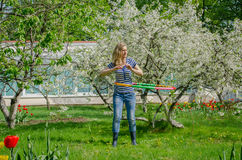 Girl turning hula hoop between flowering cherry Royalty Free Stock Photos