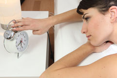 Girl turning off her clock Stock Images