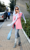 Girl turning on the sidewalk. In pink coat and with blue bag and scarf Royalty Free Stock Image