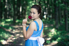 Girl turns around with red rose in her hand in the dark forest Royalty Free Stock Photos