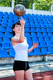 Girl turns the ball on his finger. Beautiful girl playing with a ball Royalty Free Stock Image