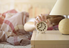 Girl turns off the alarm clock Stock Images