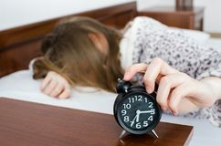 Girl turns off alarm clock royalty free stock image