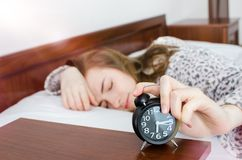 Girl turns off alarm clock royalty free stock photography